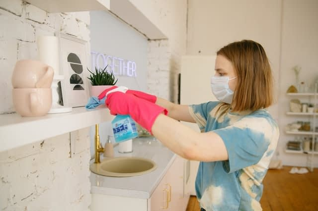 woman cleaning with a mask